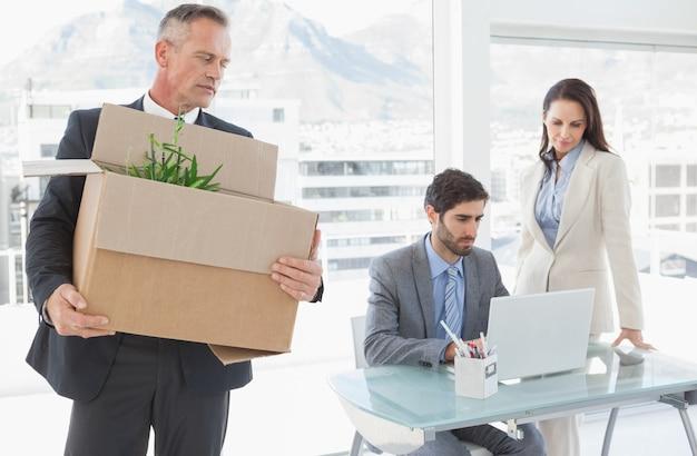 Homme d'affaires triste transportant une boîte