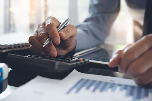 Homme d'affaires utilisant une calculatrice pour calculer les données d'entreprise au bureau