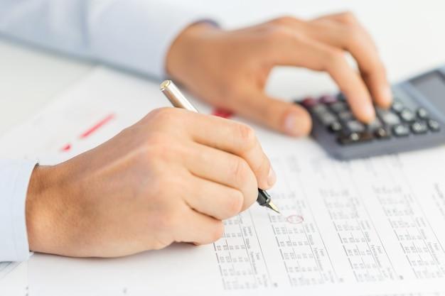 Homme d'affaires utilisant une calculatrice pour calculer les nombres