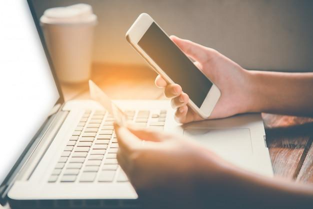 Homme d'affaires utilisant une carte de crédit et un smartphone avec un ordinateur portable pour acheter en ligne