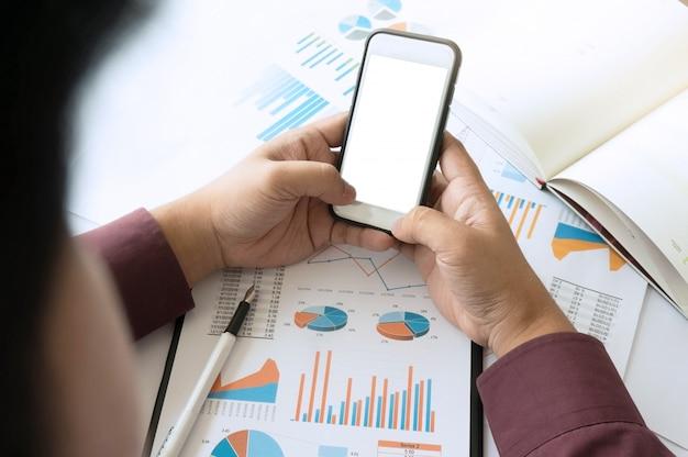 Homme d'affaires utilisant un écran blanc blanc de smartphone. travailler au bureau avec des documents sur son bureau.