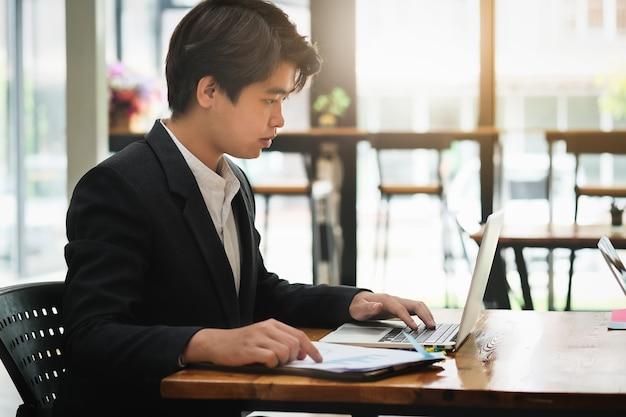 Homme d'affaires utilisant un ordinateur portable pour la recherche ou le développement marketing dans le budget de l'entreprise.