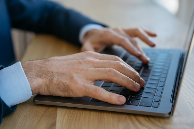 Homme d'affaires utilisant un ordinateur portable, saisie, recherche d'informations, assis au bureau. freelance travaillant à domicile