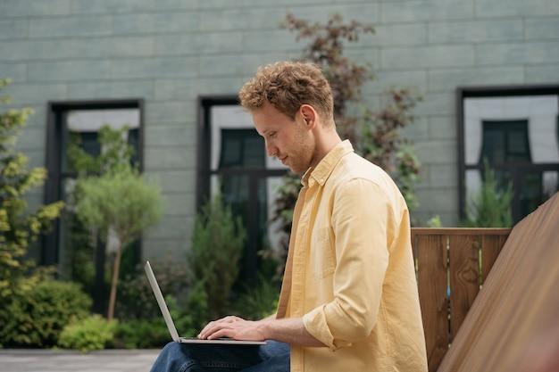 Homme d'affaires utilisant un ordinateur portable travaillant en ligne dans la rue étudiant universitaire étudiant