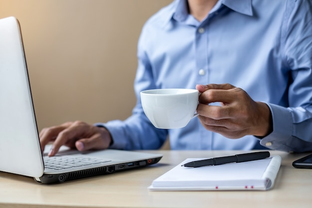 Homme d'affaires utilisant un plan marketing d'analyse d'ordinateur portable et de boire du café