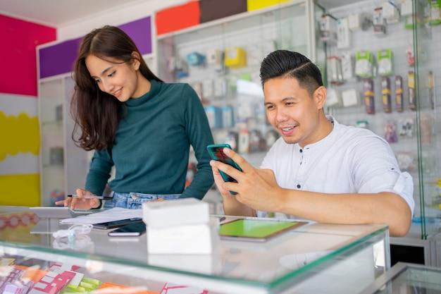 Un homme d'affaires utilisant un smartphone et une femme d'affaires utilisant une calculatrice