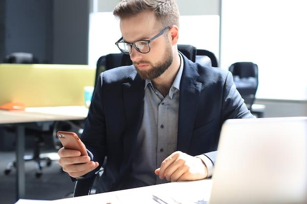 Homme d'affaires utilisant son téléphone portable au bureau.