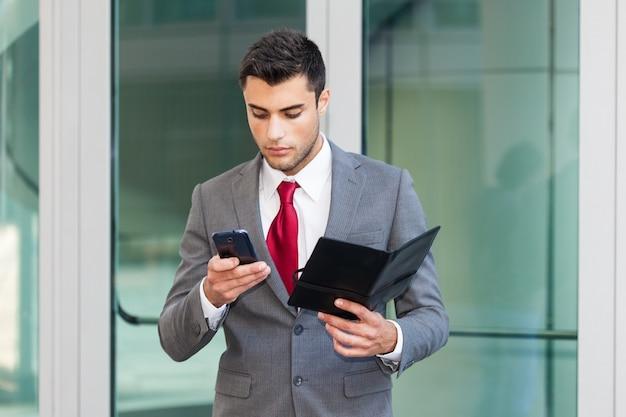 Homme d'affaires utilisant son téléphone portable en tenant un agenda