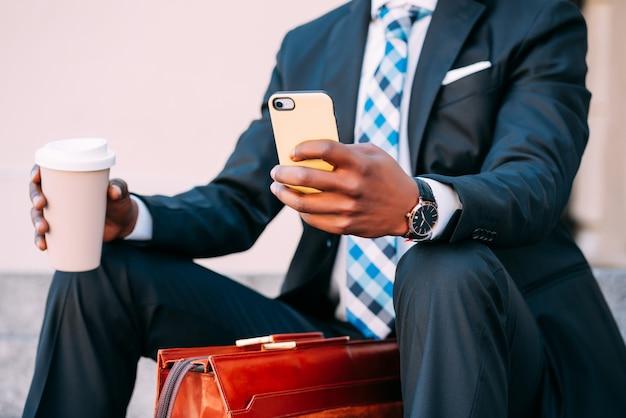 Homme d'affaires utilisant son téléphone portable et tenant une tasse de café assis à l'extérieur. concept d'entreprise et urbain.