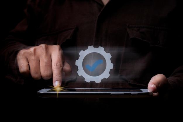 Homme d'affaires utilisant une tablette avec le service supérieur d'icônes assurance qualité, certification iso, concept d'assurance et de normalisation.