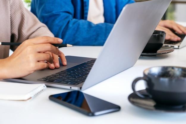 Homme d'affaires utilisant et travaillant sur un ordinateur portable ensemble au bureau