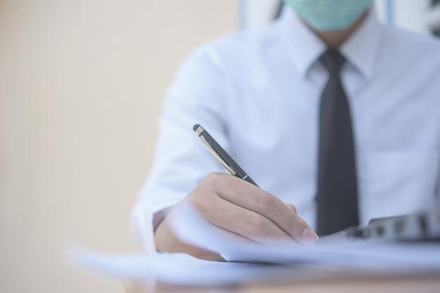 Homme affaires, utilisation, masque chirurgical, et, travailler bureau, puis, écrire, sur, document commercial