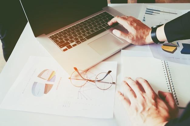 Homme affaires, utilisation, ordinateur portable, à, rapport, diagramme, dans, bureau, planification, nouveau, projet affaires