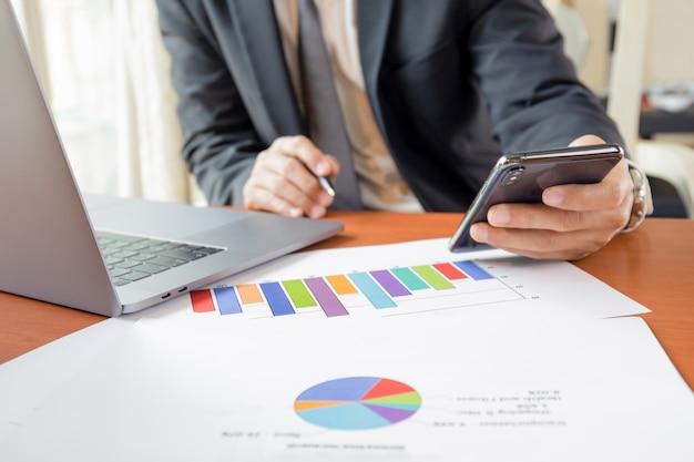 Homme affaires, utilisation, téléphone portable, à, ordinateur portable, et, graphiques, graphiques, papier, sur, table, travail, depuis, home.