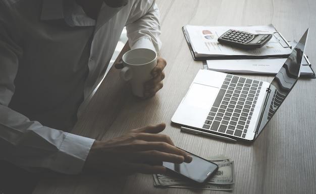 Homme d'affaires utilise l'ordinateur et mobile sur la table avec des objets de comptabilité financière