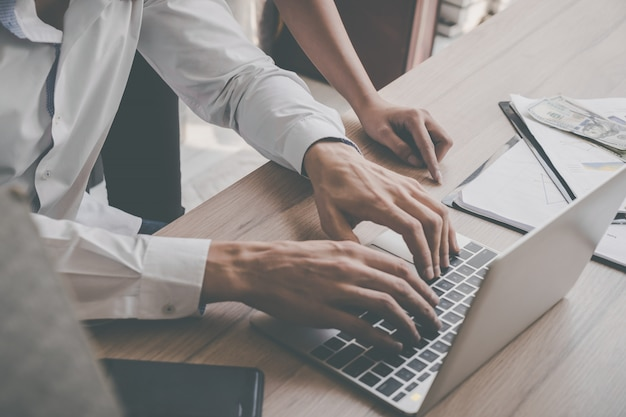 Homme d'affaires utilise l'ordinateur et le mobile sur la table avec des objets financiers aux entreprises