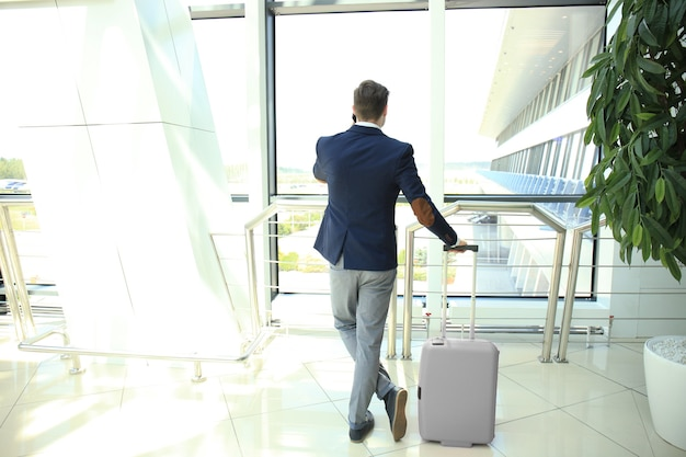 Homme d'affaires avec valise dans le hall de l'aéroport.