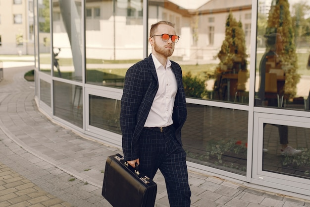 Homme d'affaires avec valise marchant dans une ville d'été