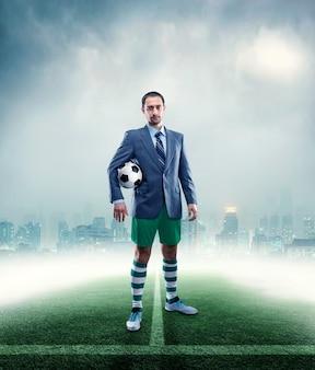 Homme d'affaires avec valise en vêtements de sport jouant au football en plein air