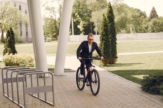 Homme d'affaires à vélo dans une ville d'été