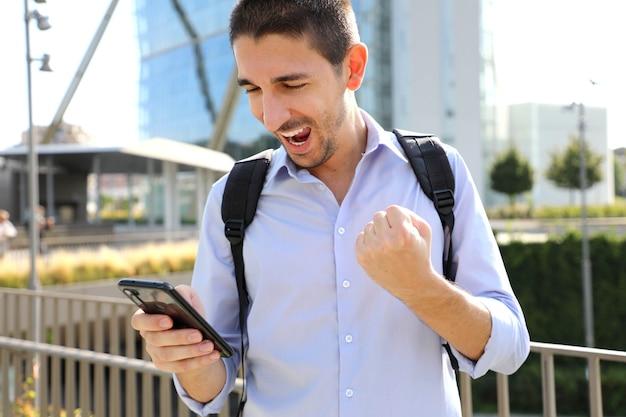 Homme d'affaires vérifiant les bonnes nouvelles sur smartphone