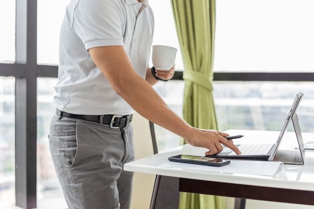 Homme d'affaires vérifiant le courrier électronique sur un ordinateur portable et tenant une tasse de café