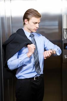 Homme d'affaires vérifiant l'heure en attendant l'ascenseur au bureau
