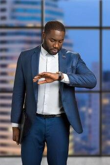 Homme d'affaires vérifiant l'heure sur sa montre-bracelet. jeune manager regarde sa montre le soir