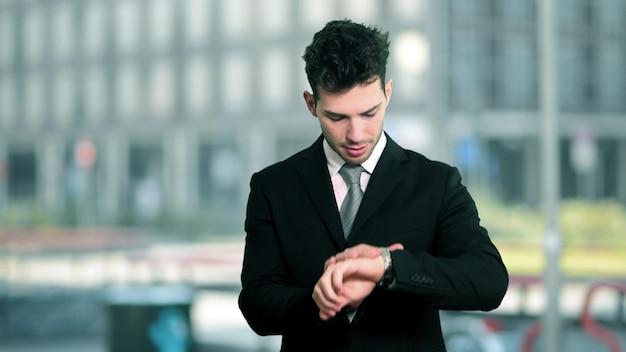 Homme d'affaires vérifiant l'heure sur sa montre