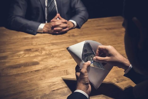 Homme d'affaires vérifiant son argent, dollars américains, dans l'enveloppe que vient de lui remettre son partenaire