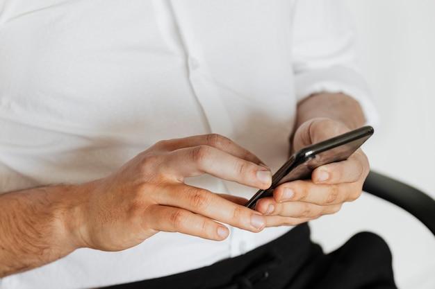 Homme d'affaires vérifiant son compte de médias sociaux et ses messages sur un téléphone