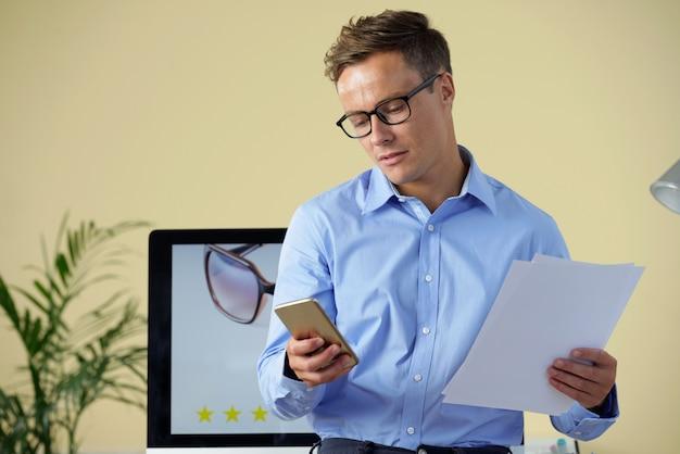 Homme d'affaires vérifiant le téléphone
