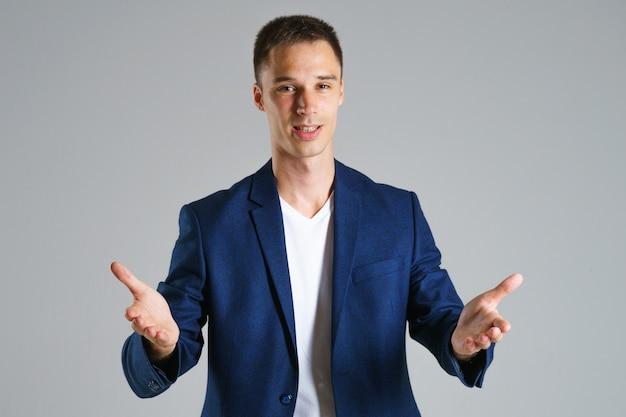 Homme d'affaires en veste bleue fait des gestes avec ses mains