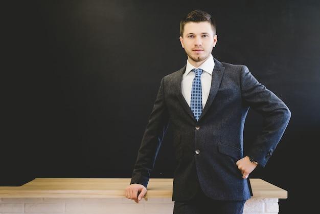 Un homme d'affaires en veste avec une cravate est à table. isolé sur fond noir