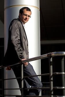 Homme d'affaires en veste grise, en jeans et lunettes classiques, est assis sur une balustrade par temps ensoleillé
