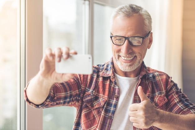 Homme d'affaires en vêtements décontractés et lunettes fait selfie