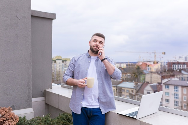 Homme d'affaires en vêtements décontractés se détendre sur la terrasse surplombant la ville utilise le téléphone et utilise un ordinateur portable tout en buvant du café