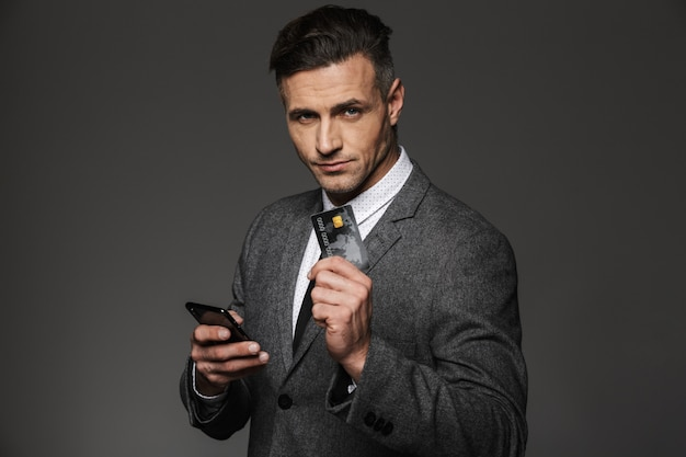 Homme d'affaires en vêtements formels démontrant une carte de crédit en plastique et tenant un téléphone portable en main, isolé sur mur gris