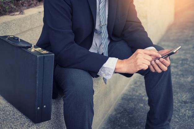 Homme d'affaires vêtu d'un costume noir et utilisant un smartphone moderne en plein air