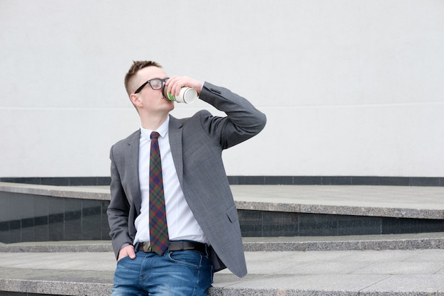Homme d'affaires, vêtu d'une veste grise, d'un jean bleu, d'une chemise blanche et d'une cravate prendre une pause déjeuner