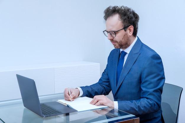 Homme d'affaires avec un visage pensif en costume bleu à l'aide d'un ordinateur portable sur fond intérieur de bureau. concept de proposer une nouvelle stratégie, un plan anti-crise