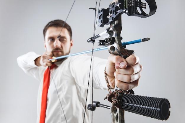Homme d'affaires visant la cible avec arc et flèche, isolé sur fond gris studio. l'entreprise, l'objectif, le défi, la concurrence, le concept de réalisation