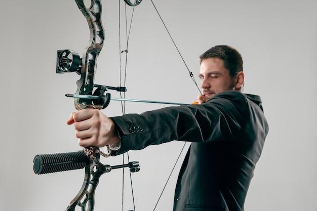 Homme d'affaires visant la cible avec arc et flèche, isolé sur fond gris studio.