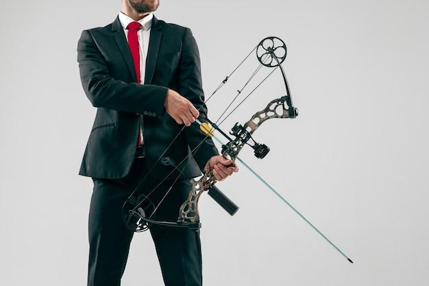 Homme d'affaires visant la cible avec arc et flèche, isolé sur fond gris.