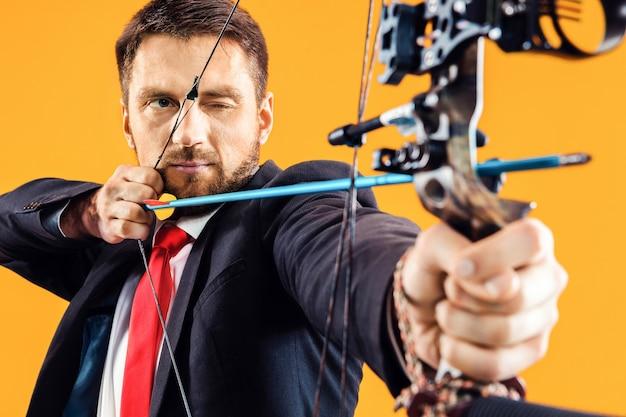 Homme d'affaires visant à cible avec arc et flèche, isolé sur fond de studio jaune. l'entreprise, l'objectif, le défi, la concurrence, le concept de réalisation