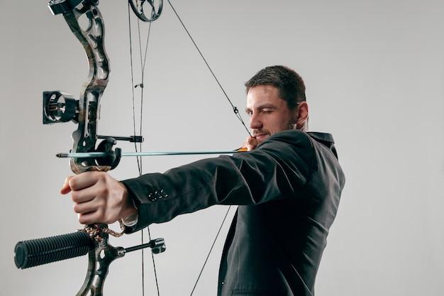 Homme d'affaires visant la cible avec un arc et une flèche, isolé sur un mur de studio gris