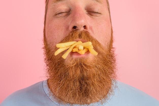 L'homme affamé avec la barbe et les tatouages mange des pommes de terre frites