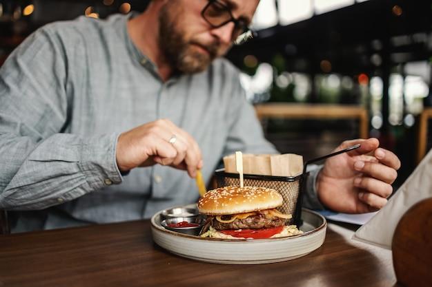 Homme affamé barbu d'âge moyen assis dans un restaurant et manger un délicieux hamburger.