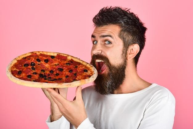 Homme affamé mangeant une pizza savoureuse. homme satisfait avec barbe et moustache dégustant une délicieuse pizza. fast food. nourriture italienne. concept de livraison de pizzas. l'homme barbu en pull blanc détient une savoureuse pizza fraîche.