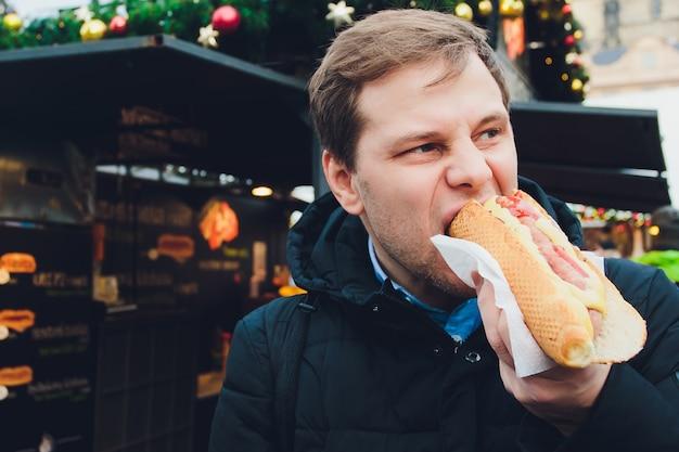 Homme affamé, manger, hot-dog, dehors